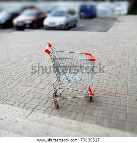 Empty shopping cart in parking lot. Useful file for your article about globalization,  etc