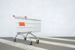 Empty Shopping Cart Trolley Stands near Mall with Copy Space. Grocery Cart on the White Wall Store. Trolley at the Supermarket Background. E-commerce. Shopping Concept. Side View. Shopping Service