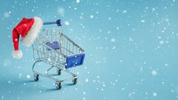 Empty shopping trolley and santa hat on blue snowy background
