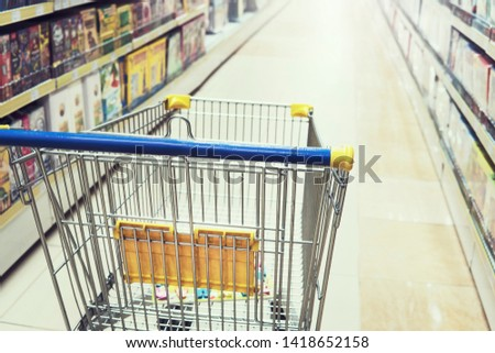Empty shopping trolley cart in shopping mall interior background. Toy store, Bookstore, household and household goods #1418652158