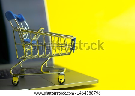 Empty shopping trolly cart on notebook keyboard with yellow space use as Get ready for online shopping concept