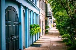 Empty sidewalk view of lush summer greenery lining the colorful Georgian architecture of the colonial Rainbow Row in the historical Battery neighborhood of Charleston, South Carolina, USA