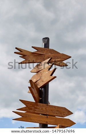 Empty sign pointers with a space for text. Wooden pointers on a wooden pole. #1479167696