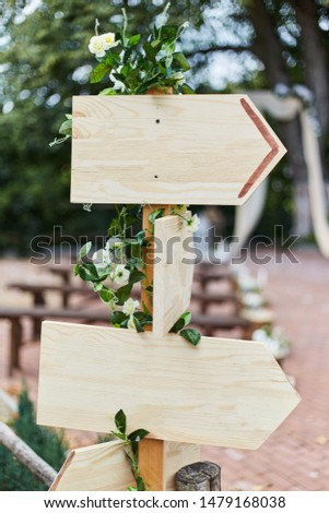 Empty sign pointers with a space for text. Wooden pointers on a wooden pole. #1479168038