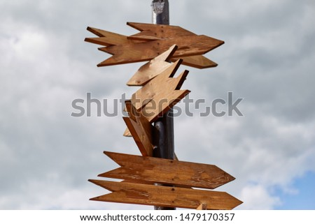Empty sign pointers with a space for text. Wooden pointers on a wooden pole. #1479170357