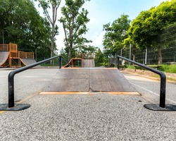 Empty skate park in summer steel framed wooden ramps, paths fences, steps, walls and trees in the background.
