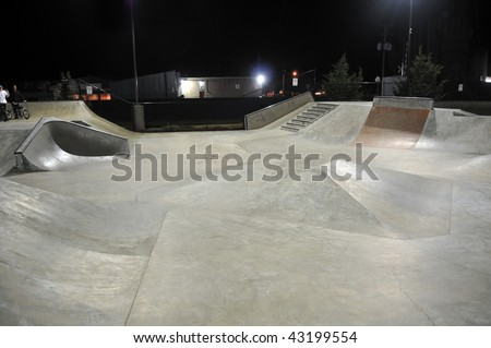 Empty skatepark at night with grind rails. Concrete cement.
