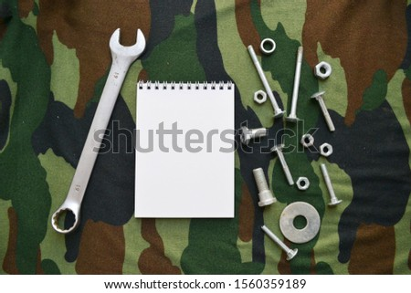 Empty sketchbook on a green background with wrench, bolts and nuts. Mockup for design with space for text. Male repair kit.