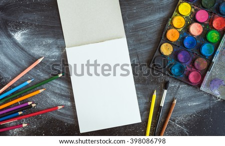 Empty sketchbook on chalk board with art supplies around. Mockup for illustration or art. stock photo