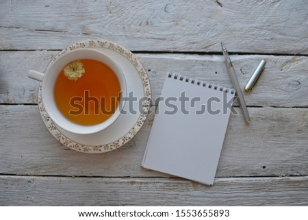 Empty sketchbook on wooden background with a cup of tea and pen. Mockup for elegant design with space for text.
