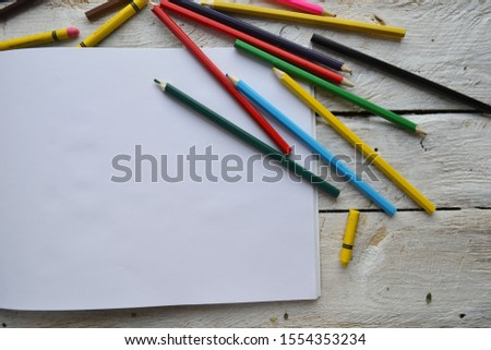 Empty sketchbook on wooden background with colorful pencils. Artist's workplace. Mockup for elegant design with space for text.