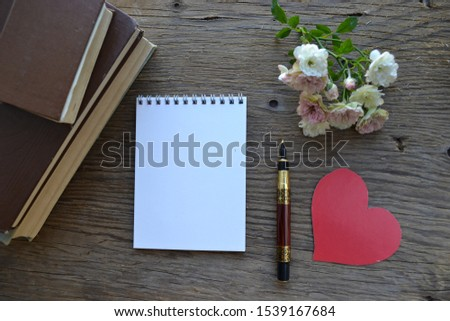 Empty sketchbook on wooden background with red valentines, roses, books and pen. Mockup for elegant design with space for text.