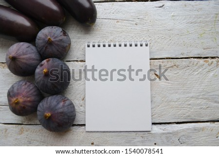 Empty sketchbook on wooden background with ripe figs and eggplant. Mockup for elegant design with space for text. View from the top, flat lay.