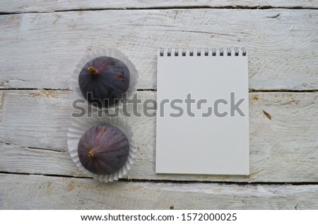 Empty sketchbook on wooden background with ripe figs. Mockup for elegant design with space for text. View from the top, flat lay.