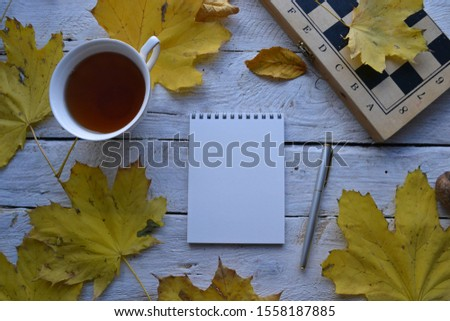 Empty sketchbook on wooden desk with a cup of tea, chessboard, maple leaves and pen. Mockup for elegant design with space for text.
