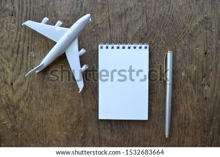 Empty sketchbook on wooden desk with  airplane model and pen. Mockup for elegant design with space for text.