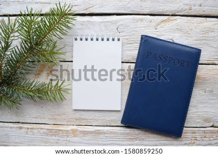 Empty sketchbook on wooden desk with  Christmas tree branch and passport. Mockup for elegant design with space for text. New Year holidays travel planning.