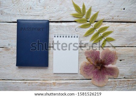 Empty sketchbook on wooden desk with passport, hibiscus and palm tree branch. Mockup for elegant design with space for text. Travel and vacation planning.
