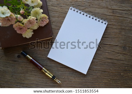 Empty sketchbook on wooden desk with  roses, book and fountain pen. Mockup for elegant design.