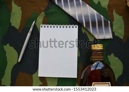 Empty sketchbook with a bottle of cognac, tie and pen. Mockup for elegant design with space for text. February 23. Men's set.