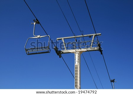 empty ski lift and tower with a blue sky background - stock photo