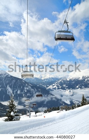 Empty ski lift in beautiful winter snowy mountain landscape (resort in Alps)