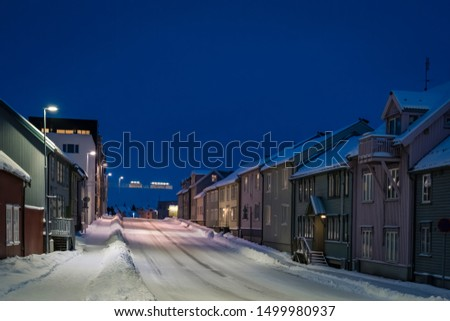 Empty slippery and covered in snow and ice residential street in Tromso at dusk, Norway