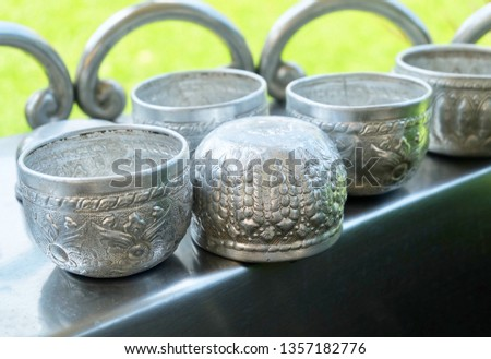 Empty Small Bowls with Thai Bas Relief in A Temple, Used to Contained Holy Water or Blessed Water to Drink, Cleaning The Body and Blessing for Protection and Good Luck.