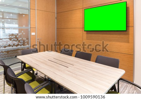 Empty small bright meeting room with blank green screen TV and flipchart. Modern design interior with six yellow chairs, wood decorated walls, glass windows and wood table.
