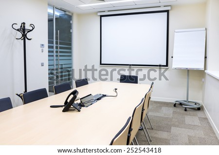 Empty small bright meeting room with TV proektor screen and flipchart. Modern design