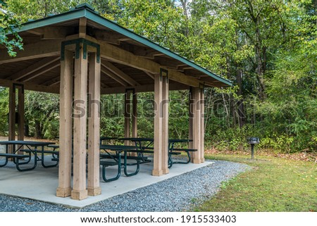 Empty small picnic pavilion with several tables on a cement pad with a grill alongside in the woodlands at the park Photo stock ©