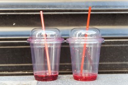 empty smoothie cups. plastic trash in a big city. leftover juice in a plastic glass