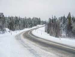 Empty snowy Northern winter road, turn on the road