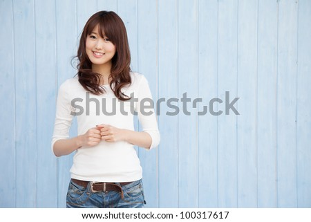 Empty space and a young Asian woman smiling blue background