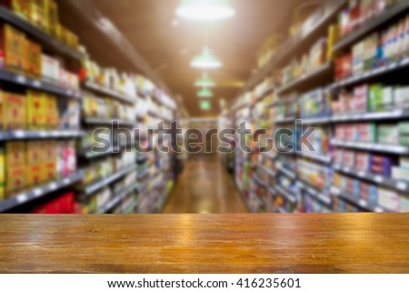 Empty space brown wooden table with blurred supermarket shelf background. Supermarket concept