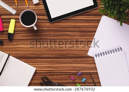 Empty space in the middle of office equipment such as digital tablet, notepad, sheet of paper, notebook, highlighter, ruler, plant and other on dark wooden office desk.