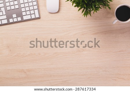 Empty space next to office equipment such as computer modern keyboard, white mouse, mug of coffee and plant on bright wooden office desk.