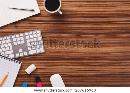 Empty space next to office equipment such as computer modern keyboard, white mouse, notepad, pencil, mug of coffee and other office equipment on dark wooden office desk.