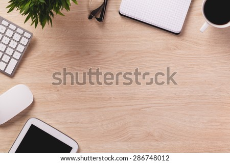Empty space next to office equipment such as computer mouse, keyboard, notepad, digital tablet and mug of coffee on wooden office desk.