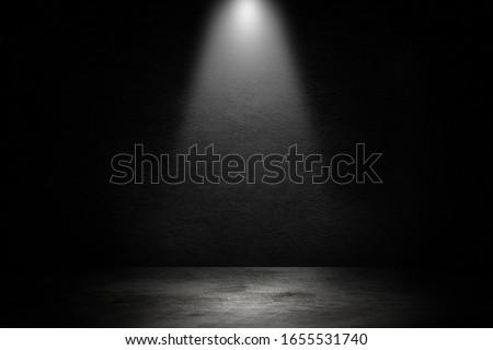 Empty space of Studio dark room black concrete wall and spotlight with concrete floor.