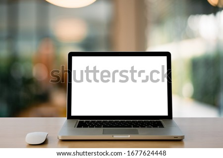 Empty space,Wooden Computer Desk and Laptop with blank screen and wireless mouse in office with modern blurred background light bokeh.- Image