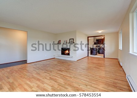 Empty Spacious Family Room Features White Walls Framing Brick