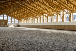 Empty spacious riding hall interior view. Sunlight through windows. Modern equestrian place.