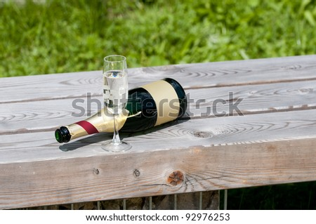empty sparkling wine bottle with glass lying on a wooden bench