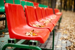 Empty sports grandstand in the leaves in the fall. Yellow leaves lie on a seat of a tribune.
