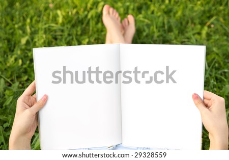 Empty spread in female hands against feet and a summer meadow
