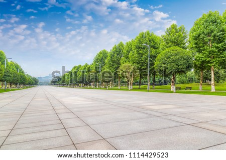 empty square and trees over blue sky. #1114429523
