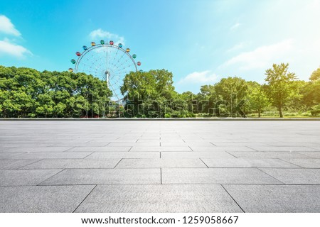 Empty square floor and ferris wheel in green city park