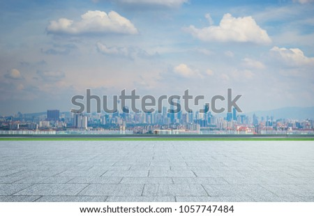 Empty square ground floor with city skyline background . Mixed media . #1057747484