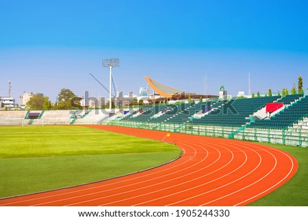 Empty stadium arena and race running track treadmill background, Bangkok, ThailandStadium arena soccer field.Landscape of soccer field with green grass, stadium and playground.